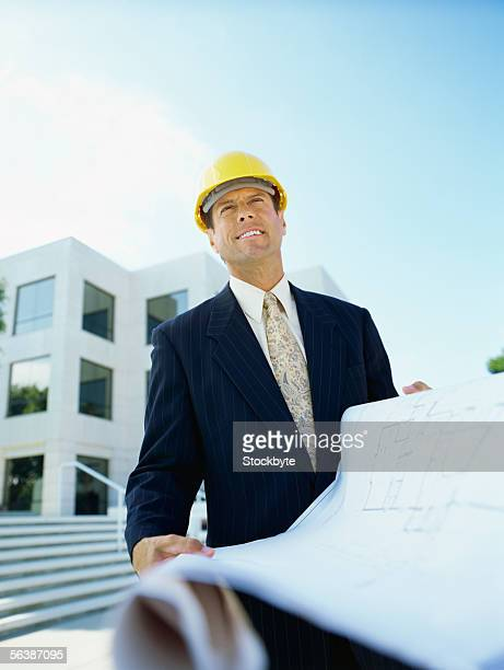low angle view of a male architect holding blueprints