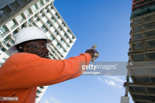 Low angle view of a male construction worker pointing towards the building : Foto de stock