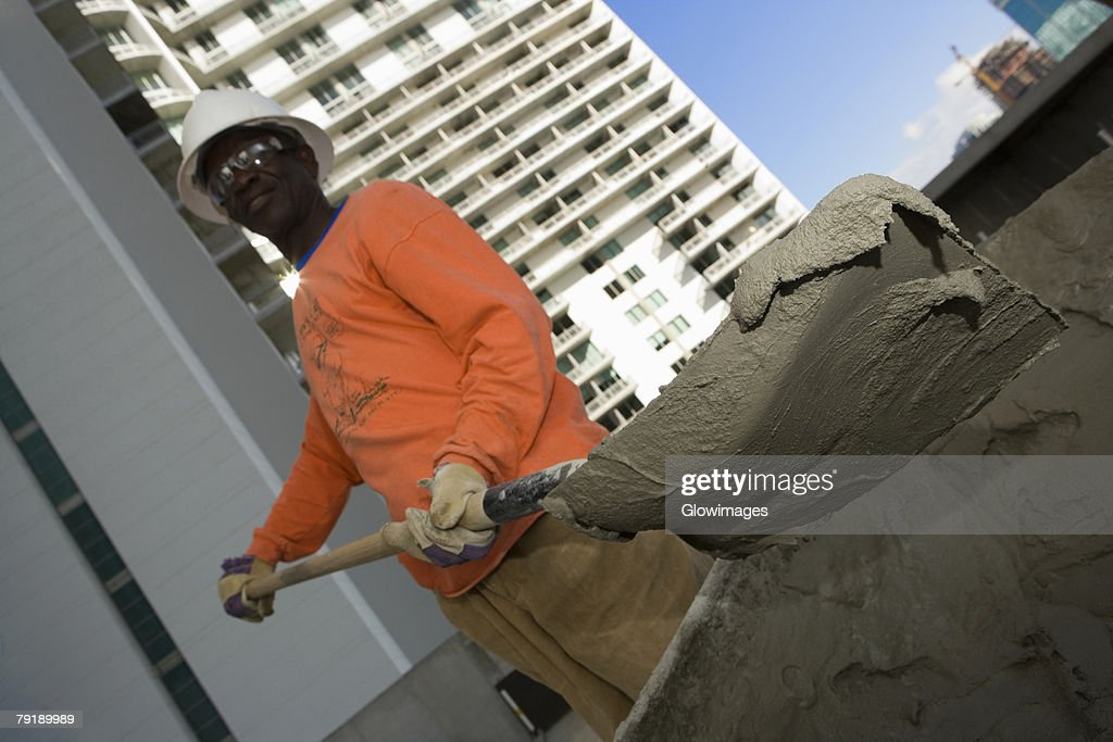 Low angle view of a male construction worker shoveling cement : Stock Photo