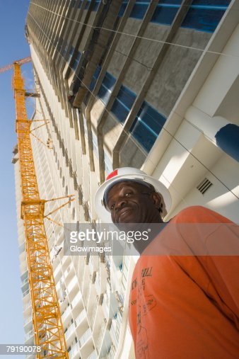 Low angle view of a male construction worker standing in front of a building : Foto de stock