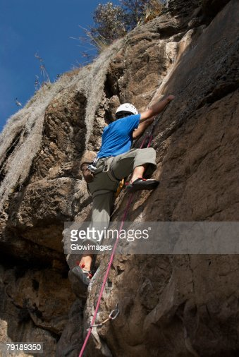 Low angle view of a male rock climber scaling a rock face : Foto de stock