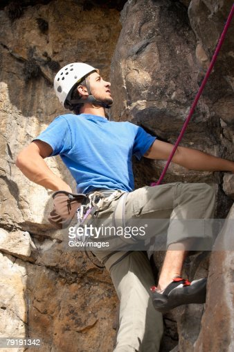 Low angle view of a male rock climber scaling a rock face : Stock Photo