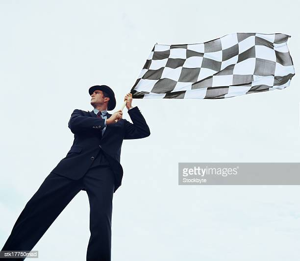 low angle view of a man holding a checkered flag