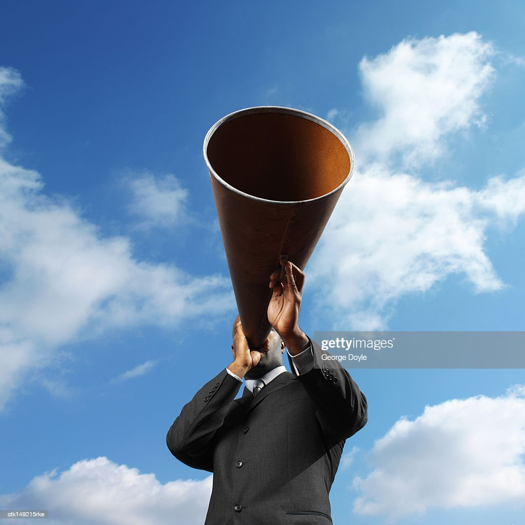 low angle view of a man holding a loudspeaker : Stock Photo