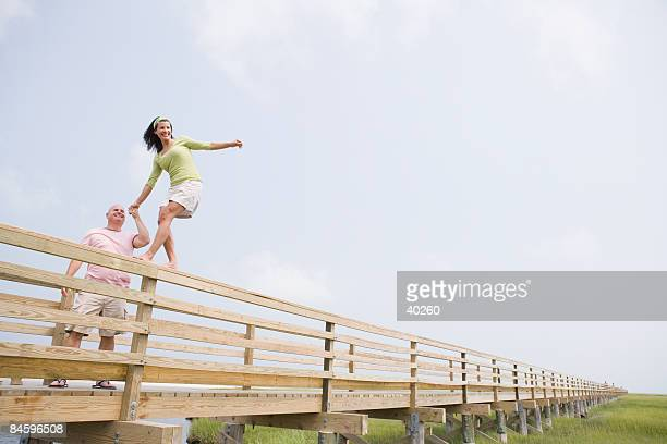 Low angle view of a mature woman walking on a fence with a mature man holding her hand