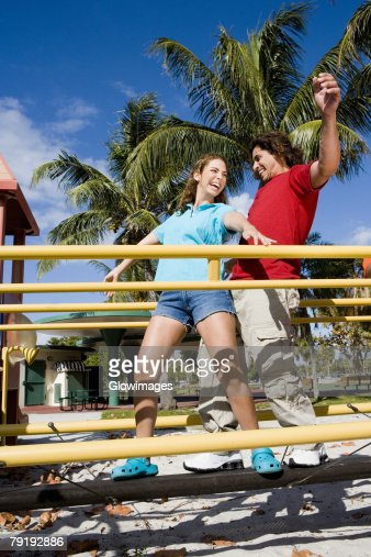 Low angle view of a mid adult couple standing on a jungle gym and smiling : Stock Photo