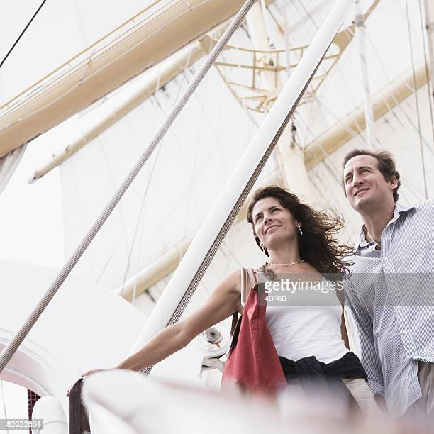 Low angle view of a mid adult couple standing with their arms outstretched