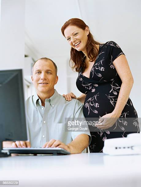 low angle view of a mid adult man and a pregnant woman looking at the computer