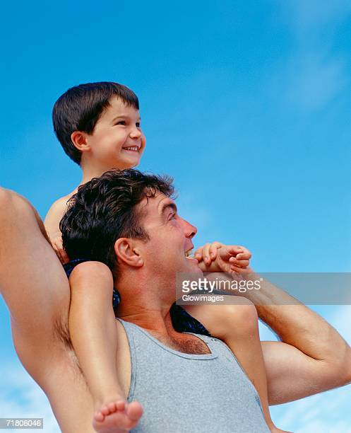 Low angle view of a mid adult man carrying his son on his shoulders, Bermuda