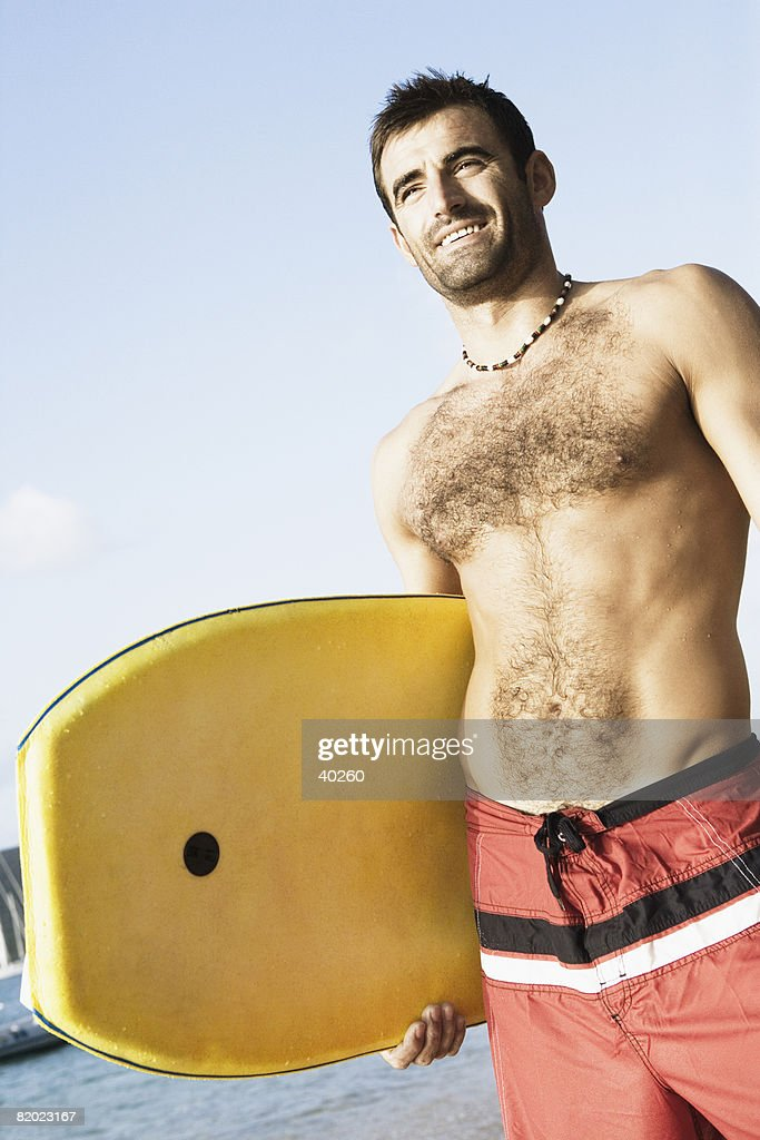 Low angle view of a mid adult man holding a surfboard : Stock Photo