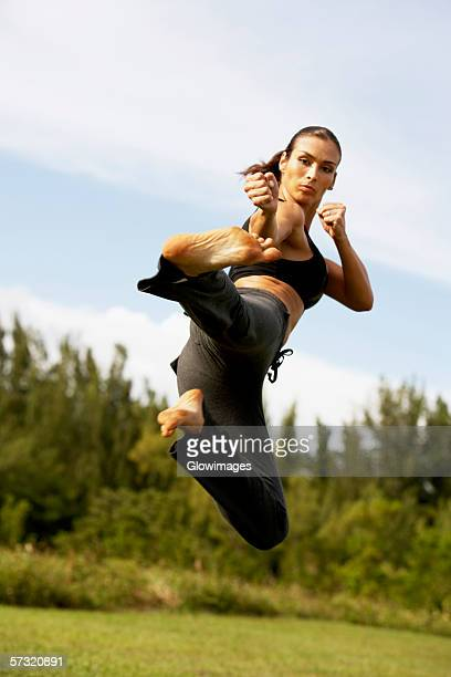 Low angle view of a mid adult woman practicing martial arts