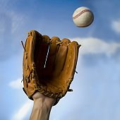 Low angle view of a person's hand catching a baseball with a baseball glove