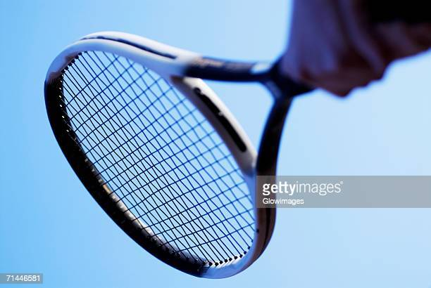 Low angle view of a person's hand holding a tennis racket
