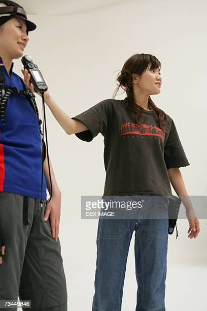 Low angle view of a photographer using a light meter in front of a female fashion model