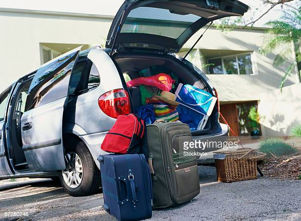 Low angle view of a pile of luggage near the open boot of a car