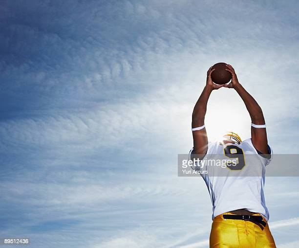 Low angle view of a rugby player holding ball up