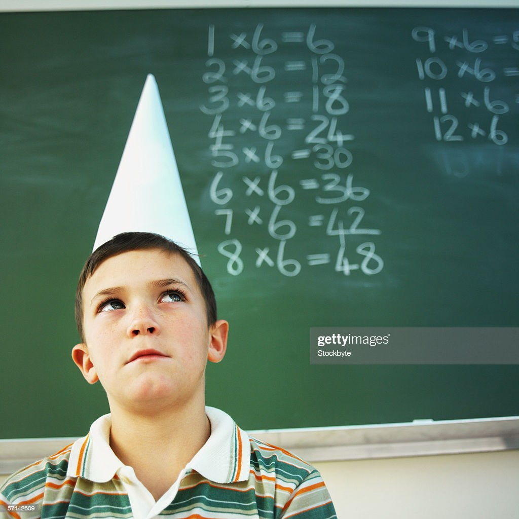 Low angle view of a schoolboy (8-9) wearing a dunce cap
