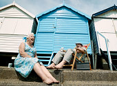 Low Angle View of a Senior Couple Sitting in Front of Beach Huts, Laughing