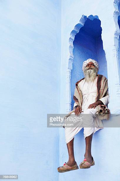 Low angle view of a senior man sitting on an arch window, Pushkar, Rajasthan, India