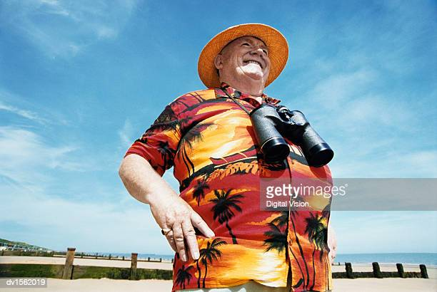 Low Angle View of A Smiling Senior Man Wearing a Hat and Binoculars