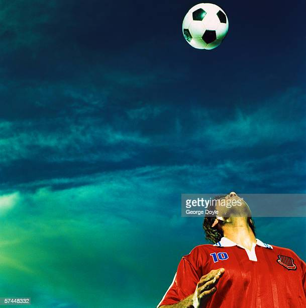 low angle view of a soccer player attempting to head a ball