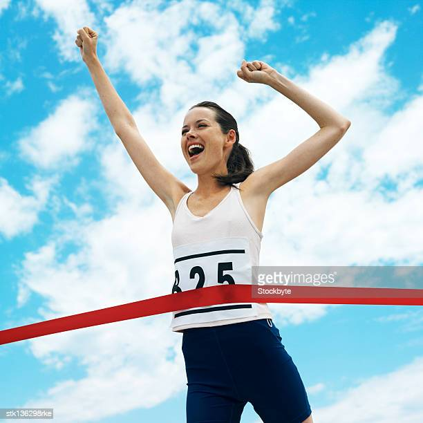 low angle view of a woman cheering at completing a race