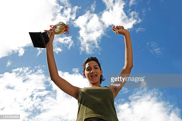 Low angle view of a woman holding a trophy