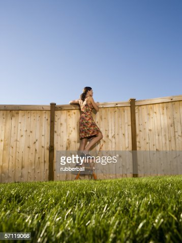 Low angle view of a woman peeking over a wooden fence