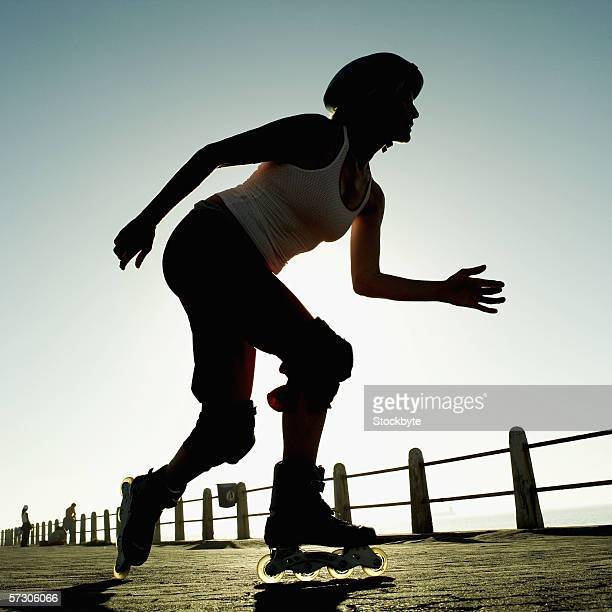 Low angle view of a woman rollerblading on a pier
