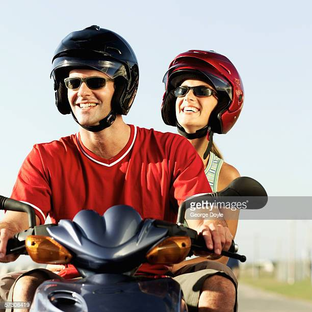 Low angle view of a young couple on a scooter wearing helmets