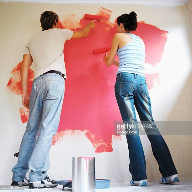 Low angle view of a young couple painting a wall with paint rollers
