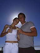 Low angle view of a young couple standing outdoors with drinks