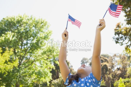 Girl holding up two American flags at park