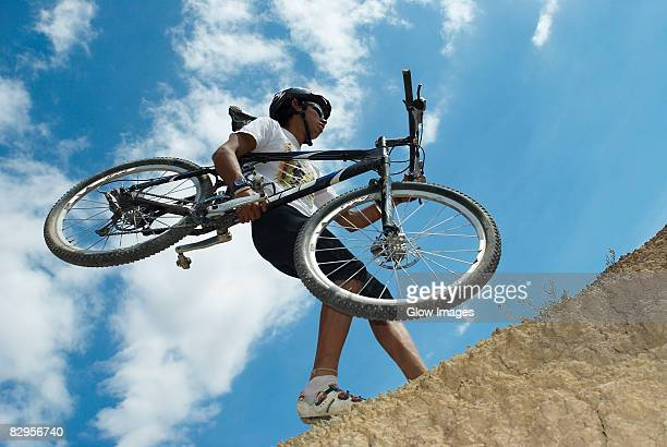 Low angle view of a young man carrying a mountain bike