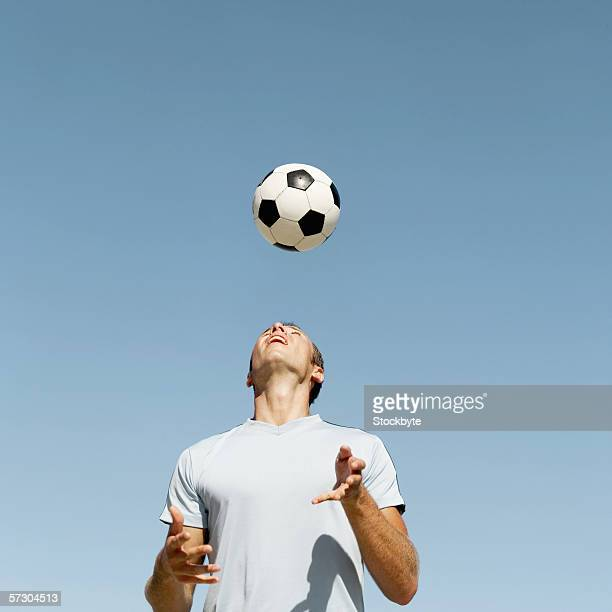 Low angle view of a young man headering a soccer ball