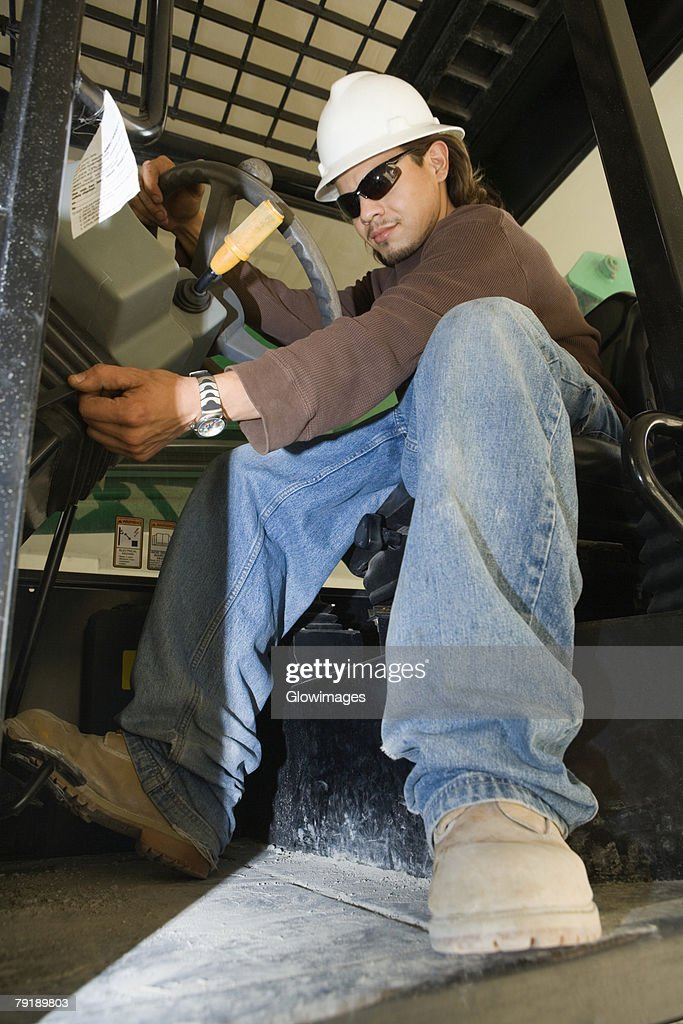 Low angle view of a young man operating a crane : Foto de stock