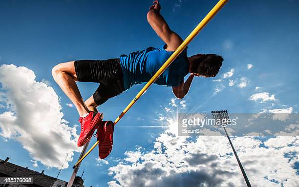 Inquadratura dal basso di un giovane uomo eseguendo salto in alto.