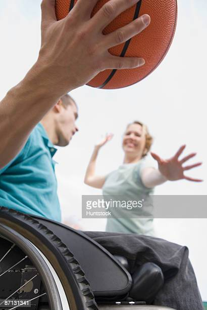 Low angle view of a young man sitting in a wheelchair and playing basketball