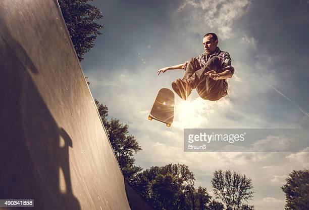 Low angle view of a young man skateboarding outdoors.
