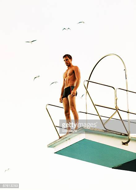 Low angle view of a young man standing on a diving board