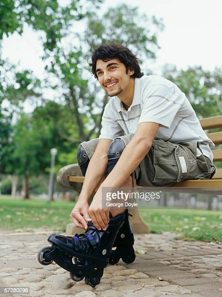 Low angle view of a young man tying laces of inline skates