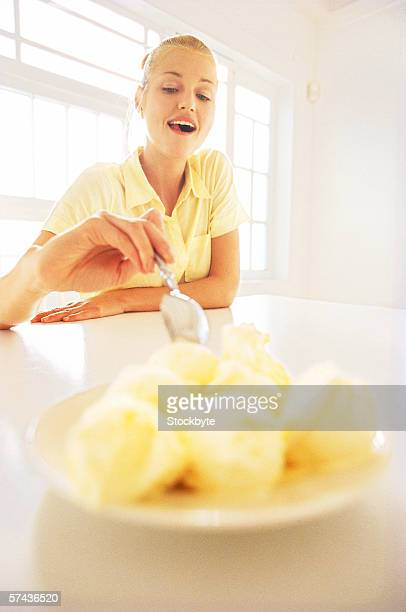 low angle view of a young woman eating a plate of ice cream