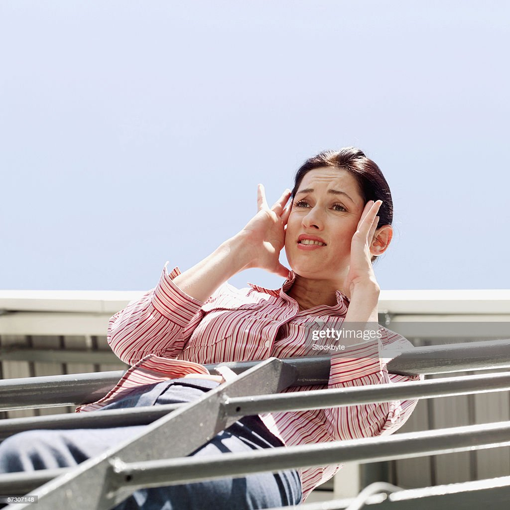 Low angle view of a young woman leaning over a railing holding her head : Stock Photo