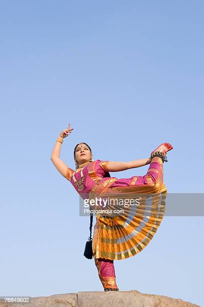 Low angle view of a young woman performing Bharatnatyam on a rock