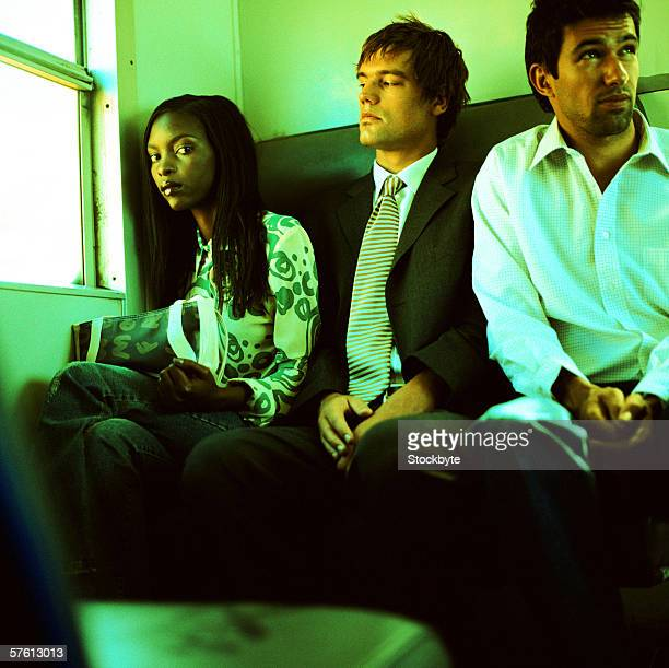 Low angle view of a young woman sitting with two young men in a train (toned)