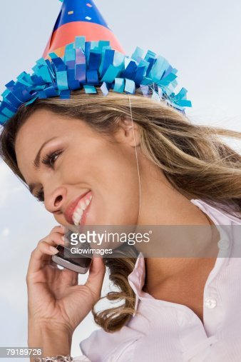 Low angle view of a young woman talking on a mobile phone and smiling : Foto de stock
