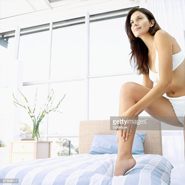 Low angle view of a young woman wearing lingerie and applying lotion to her leg