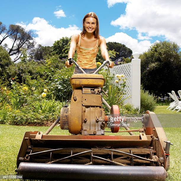 low angle view of a young woman with an electric lawn mower mowing the lawn