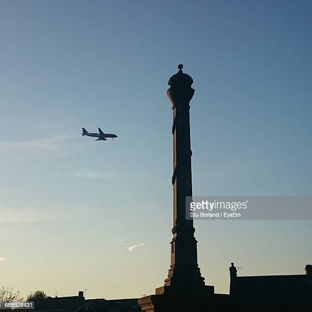Low Angle View Of Airplane Flying By Monument Against Sky