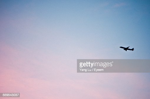 Low Angle View Of Airplane Flying In Sky At Sunset